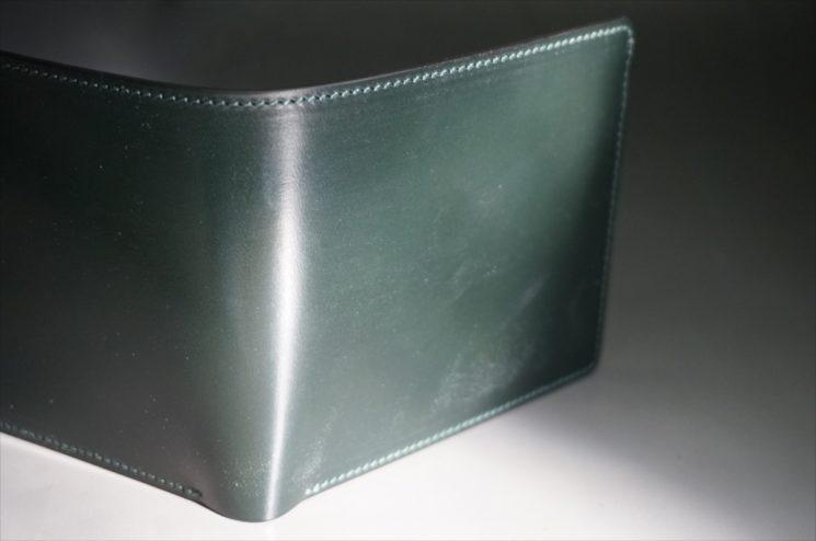 日光の下で見たダークグリーンのブライドルレザーの二つ折り財布